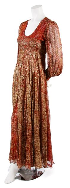 A Thea Porter Red Chiffon Moroccan Style Dress, 1960s, with all-over metallic and sequined embroidery, set in sheer sleeves with snap closures, scoopneck, empire waist, full length skirt, fully lined. Labeled: Thea Porter Couture.