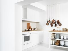A small white kitchen consisting of a complete base cabinet with doors, drawers, worktop and a wall cabinet with doors.
