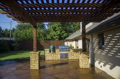 Cedar arbor lending shade to a large designer patio, with an outdoor kitchen on the perimeter. Designed and installed in Oklahoma City, OK by Red Valley Landscape & Construction.