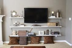 "tv mounted on wall surrounded by floating shelves supported by chain link. Movies in one basket and power cords in another. Great idea !! #""tvwallmountdecor"""