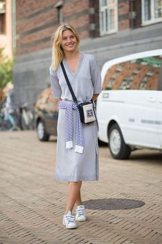For a summery European look, style your sneakers with a loose knit midi dress—bonus points when you take it up a notch by tying a striped sweater around your waist.