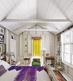 """Master bedroom in an updated farmhouse in East Hampton uses bright colors in…"