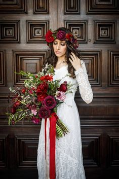 Red bridal bouquet and flower crown with peonies, roses, and ranunculus by ella & louie.