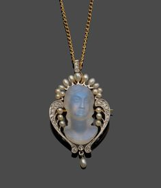 An Art Nouveau Brooch/Pendant, a carved moonstone as a maiden's head, within a diamond and seed pearl frame, with a detachable diamond set pendant loop, on a fine trace link chain, brooch/pendant measures 2.4cm by 4.4cm, chain length 43cm Tennants Auctioneers: An Art Nouveau Brooch/Pendant