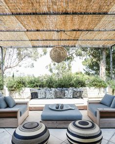 The guest house patio is under a reed and steel arbor and features teak outdoor furniture by James Perse.