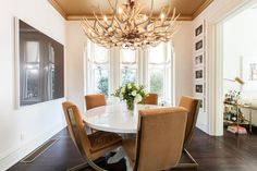 An antler chandelier lends an organic touch in the sleek dining room of a San Francisco home owned by Jessica and Matt Farron and designed by Leanne Ford.