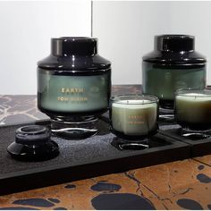Inspired by the ancient ideology of reducing all matter to four bare elements, the medium-sized 'Earth' scented candle from the Tom Dixon Elements Candles collection features a mossy, evergreen scent, accentuated by delicate aromas of green leaves, mint and guaiac wood. The candle is housed in a glass container with a simplistic brand logo to the front.  Top Notes: Green leaves, Mint Heart Notes: Galbanum Resinoide, Humus Accord Base Notes: Guaiac Wood, Cedarwood  Burn Time: 40mins  Made in… Tom Dixon, Almirah Designs, Portable Bathroom, Room Hire, Perfume, Shower Panels, Luxury Candles, Candels, Pots
