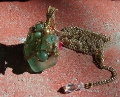 Gifted to Lynda S. - Lynda gave me a piece of light green ocean glass which I wove with a gold tone wire front and back. One side was then embellished with Green Adventurine, a couple of pearls and tiny Lucite flowers with Swarovski bicones, and a large, semi-transparent green Lucite leaf.  The reverse side was encrusted with round, radiant Red Agate of different sizes, more Lucite flowers and Swarovski bicones, and lots of bling from the clear, facetted glass beads.  ENJOY:)
