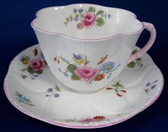 This is aShelley china, Englandtea cup and saucer in the Rose And Red Daisypattern number 13425 in the Dainty shape with pinktrim made in 1940-1966. Thebon