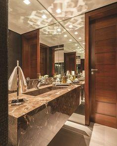 Lavabo sofisticado, com bancada e bojo esculpido em mármore marrom imperial da…