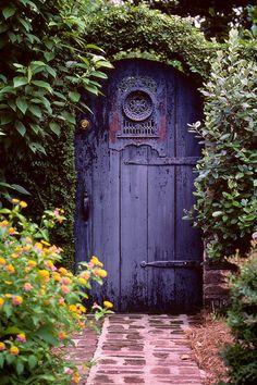 Garden walkway with an ivy arch around the door.