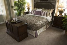 Compact bedroom featuring dark wood end table and dressers, stone facade behind head rest, and triangular patterned comforter.