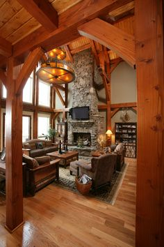 Masterful stone fireplace soaring in a timberframe living area.