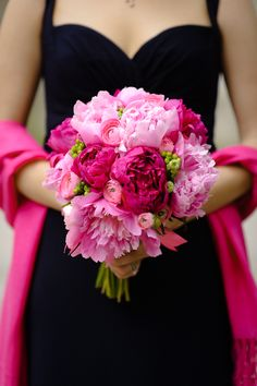 Pink and hot pink peonies, green hypericum berry, and ranunculus.