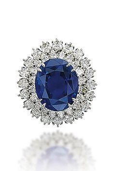 A SAPPHIRE AND DIAMOND RING, BY HARRY WINSTON  Set with an oval-shaped sapphire, weighing approximately 26.33 carats, to the marquise-shaped diamond two-row surround, mounted in platinum and gold, 5¾ with ring sizer Signed Winston and with maker's mark of Jacques Timey for Harry Winston