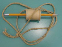 Photo of wooden spool, pencil and string.
