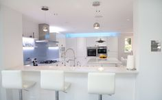 White Gloss Nolte Kitchen with bright blue glass splashbacks and ambient lighting German Kitchen, Kitchen Manufacturers, White Gloss Kitchen, Glass Splashback, Kitchen Splashback, Kitchen, Blue Glass, Bespoke Kitchens, Home Decor