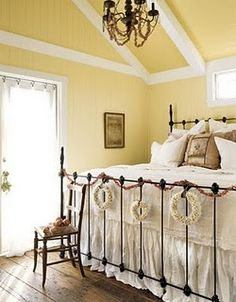 Cottage Christmas bedroom in pale yellow with beamed ceilings and wrought iron bed