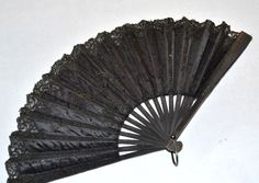 Mourning Fan: ca. late 1800's, silk adorned with tiny sequins, trimmed in lace, folds for storage with a metal ring, silk attached to painted wood with carved accents.