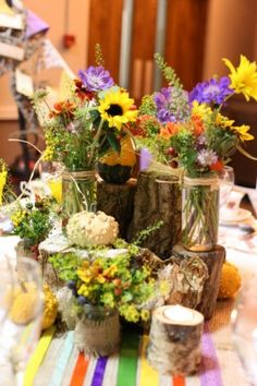 Rustic theme welsh wild flowers in jam jars on tree stumps - flowers by @Verity Cameron Cameron sidgwick. This is so perfect
