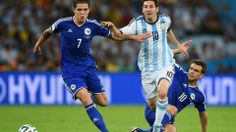 Lionel Messi of Argentina dribbles past Muhamed Besic of Bosnia and Herzegovina