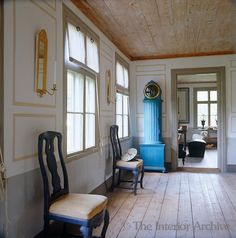 The entrance to a study is situated at one end of this country dining room and is flanked by a blue-painted antique grandfather clock