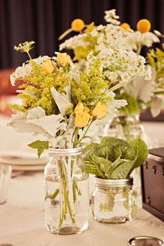 Let's do real flowers for the table tops. We can use mason jars and fill them with some nice yellow flowers and green foliage.