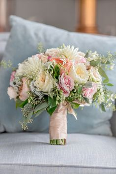 Blush roses, pink and white Peruvian lilies, white mums, daisies eucalyptus and other greens. Could also use pink or white tulips. - All would be in season in April and would readily accessible from supermarket florists or wholesalers for much cheaper than a florist.