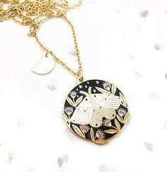 A little moth dancing in the night features on this sweet pendant, which is an original design by Lee Foster-Wilson.  It has been picked out in shiny gold metal and enamelled in black and purple and comes swinging on a gold plated trace chain which is adorned with a small shell moon...The