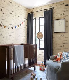 This nautical wall covering, which features line drawings of sailing ships is at once very little boy and oh-so grown up. Thanks to the room's sophisticated color foundation of cream and brown-black, the decor will have life beyond the baby years. Swaths of solid blue linen (on the glider and the curtains) envelop the space in soothing, masculine shades. The strand of alpaca wool bunting finishes off the serene space with a playful note in this California bungalow.     - CountryLiving.com