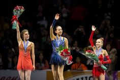 Gold medalist Mao Asada of Japan, silver medalist Ashley Wagner (L) of the United States and bronze medalist Elena Radionova of Russia wave ...