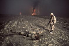 Persian Gulf War (1991). Soldier standing over a dead body, with oil fields burning in the background