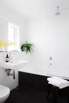 "Hugh created a boxed-out shelf along one wall to fill dead space and provide for an in-wall cistern. The floor is in matt charcoal hexagonal mosaic tiles that extend up the side of the bath.   The **ledge** is made from [Carrara](http://www.carrara-marble.com.au/|target=""_blank"") marble.: [object Object]"