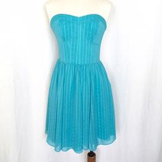 """Guess Strapless Chiffon Dress✨Host Pick✨ NWOT Beautiful turquoise/aqua strapless dress with silver metallic highlights. The top is bustier style with full skirt gathered at the waist. The sides are smocked so there is room to stretch and breath! The bodice has some boning for structure. Back invisible zipper. 99% polyester/1% metallic. Size 6. Bust: 15"""" flat across, unstretched. Waist: 13.5"""" across, unstretched. Length: 27"""" from center back to hem. Guess Dresses"""