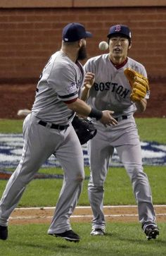 Boston Red Sox first baseman Mike Napoli tosses the game ball to relief pitcher Koji Uehara (19) after Boston defeated the St. Louis Cardinals 4-2 in Game 4 of the World Series Sunday, Oct. 27, 2013, in St. Louis. (AP Photo/Charlie Riedel)