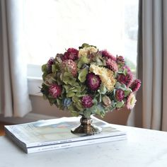 "Judes Dried Flowers is a multicolor dried floral design that showcases the bright colors and deep tints that can be retained in dried flowers. It has green hydrangea, peonies, strawberry-hued strawflowers, and nigella. It would be beautiful in a foyer or as a centerpiece.  Vase: 4"" H x 5"" W. Total height: 9""  We source our dried flowers from American growers predominately located in California and the Pacific Northwest. This reduces our carbon footprint, supports American farmers and builds…"