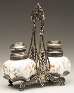 CONCAVE PANEL PAIR OF SALT AND PEPPER SHAKERS, opaque white, polychrome floral decoration and matching, period two-part lids. Fitted in a quadruple-plate stand marked for the Meriden Britannia Company. Late 19th/early 20th century