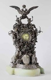 Ordered for the 25th wedding anniversary of Alexander III and Empress Maria Fedorovna. The clock is the largest masterpiece ever made by Fabergé, and it is comprised of 25 silver cupids on a pedestal. In the pedestal base is a griffin holding the Romanov family emblem in one hand and the Danish national emblem in another. The clock was a gift from 32 members of the Imperial Family, and their names are engraved on the reverse side. A monogram inlaid with diamonds was lost in the 1917…