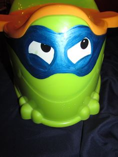 """Painting a mask on my son's once """"froggy"""" potty, transformed it to a cool ninja turtle to coincide with his changing interests.  I used a paint pen, then sealed it with clear nail polish.  I also put his name on the side and traced his hands on the back.  Then colored them in using the same technique.  Hopefully this creates more desire to do his big boy stuff."""