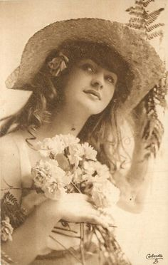 woman holds flowers to her breast, has hat and flower on her right ear, faces & looks front, faint image of left arm & hand holding hat