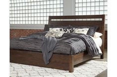 For fans of urban industrial design, the Starmore queen panel bed clearly steals the show. Its blend of acacia veneer and wood is beautified with an oiled walnut-tone finish for a highly contemporary aesthetic with natural, grainy character. Open plank detailing on the headboard and low-profile footboard perfect the look from head to toe. Mattress and foundation/box spring sold separately.
