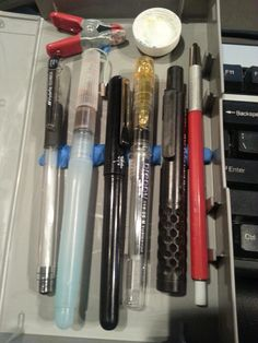 02/01/2014-  Left to Right: Hybrid Technica 04, Waterbrush, Pentel pocket brush, Preppy Fountain Pen, Cretacolor lead holder & Koh-i-noor technigraph lead holder.  Top is a soda cap filled w/white watercolor.  All are stuck to the surface w/wall-poster sticky stuff.  Running away from home kit.