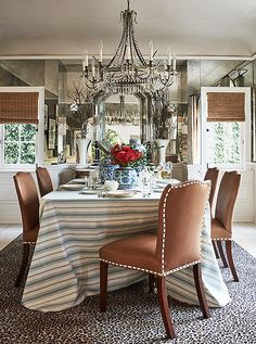 """Adding extra character in this glam dining room are leather-covered chairs, a cheetah-print rug, and an antique chandelier. """"Everything kind of glistens and shines in here,"""" says Mark."""