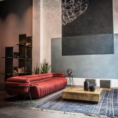 Une belle association du rouge usé du canapé et du sol en béton qui souligne l'esprit industriel du loft
