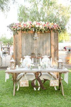 Rustic wedding idea for sweetheart table - wood barn door backdrop + pink flower garland {Leah Marie Photography}