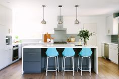 Aqua bar stools from Blu Dot punctuate the remodeled kitchen with a sense of fun.