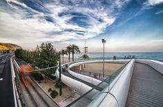 Pasarela del Postiguet I Haciendo equipo con el interiorista Oscar Vidal, se propuso una actuación que respetara la estructura de la pasarela existente redefiniendo su lenguaje estético, dotándolo de dinamismo y fluidez. Una unión entre ciudad y mar concebida como una amable curva envolvente que variase su sección a lo largo de la pasarela y acentuara el movimiento de todo el conjunto. Un acogedor gesto de bienvenida al mediterráneo. #Imaginarte #Photography #Tourism #Alicante #Spain