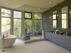 Huge windows and a stone wall help bring the outside in. I love the addition of the boulder in the shower as a natural way of providing a structure to sit or stand. The matching shapes of the basin sinks and freestanding tub provide an uniform look, while the tub itself doesn't block much light from entering the room.