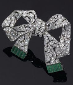 Emerald, diamond, platinum and gold brooch, circa 1910. Designed as a ribbon bow, the fully pierced brooch set throughout with diamonds, the ends of the ribbon set with emeralds, mounted in platinum and gold. #BelleEpoque #brooch