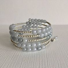 A wrap around beaded bracelet hand crafted with bright silver toned and pale smoky blue beads. The wrap around bracelet will wrap around your wrist because it is made with memory wire and adjusts to just about any size wrist and will retain its shape. You won't have to worry about